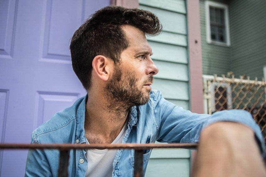 """portrait sérré de l'artiste Hugh Coltman devant une maison bleu pour la promotion de son album 'Who's Happy ?"""""""